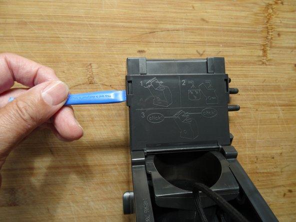 Entferne die Abdeckung am oberen Kolben. Greife links und rechts unter die Rasten, ein Plastikwerkzeug ist hilfreich, es geht aber auch mit den Fingern. Löse die Abdeckung ab.