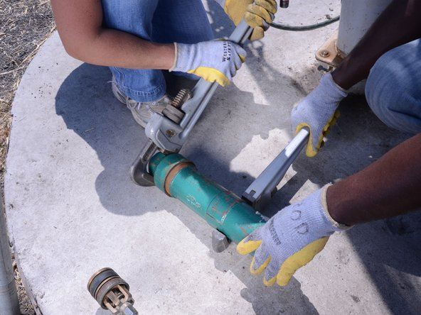 Using two pipe wrenches, remove the end cap from the cylinder.