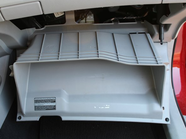 Gently lower the glovebox to the floor. It should hang in the position shown.