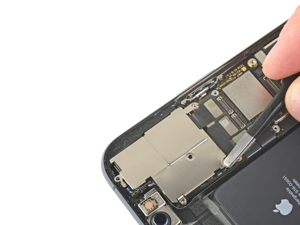 Lift the camera cover from the edge closest to the battery, and remove it.