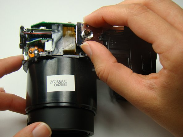 Remove the silver tripod mount by sliding it towards the speaker.