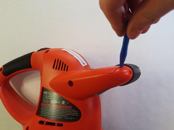Using the plastic tool, detach the handle tab as shown.