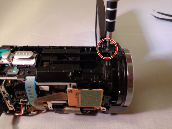 Remove the 5 mm screw from the top left near the lens of the camera.