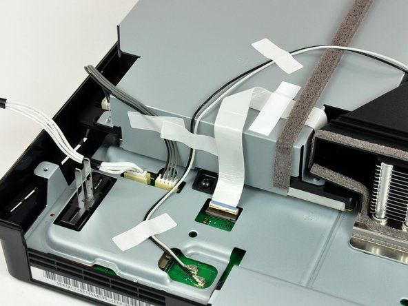 If present, remove the pieces of tape securing the antenna cables to the fan shroud, Blu-ray drive, and top shield.