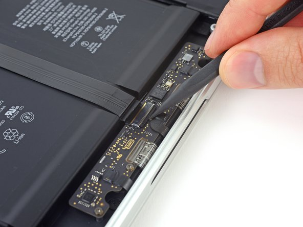 Use the tip of a spudger to flip up the black locking tab on the trackpad ribbon cable ZIF connector.
