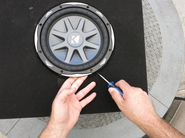 Use a flat pry tool (such as a flat-blade screwdriver) to prop up an edge of the subwoofer.