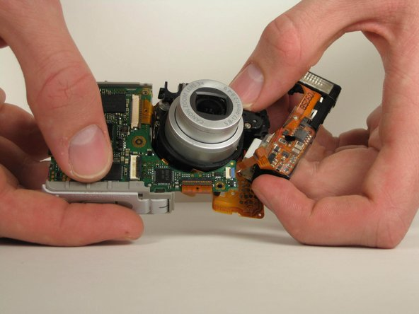 Use your fingers to give a small gap of space between the bottom of the lens assembly and the motherboard.