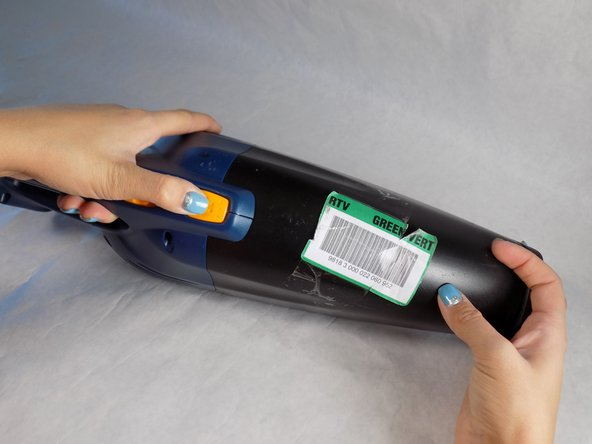 Pull the black nose off of the body of the vacuum, by pushing in the orange button closest to the nose.