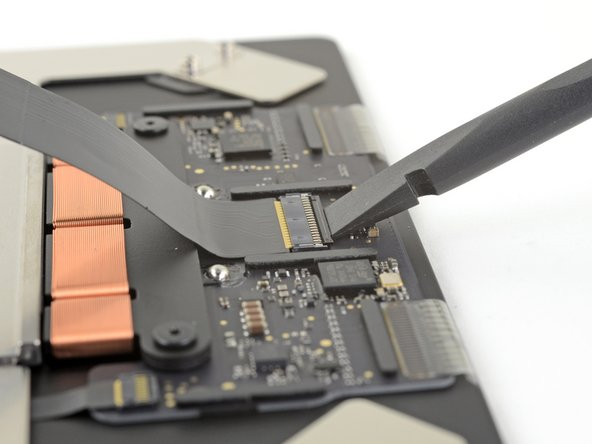 Use the flat end of a spudger to lift the small locking flap on the trackpad's ZIF connector.