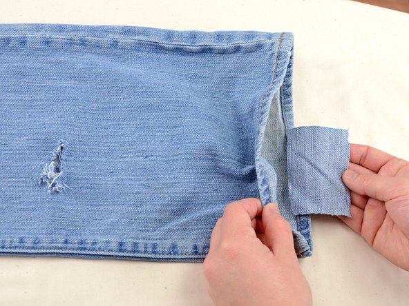 Insert the rectangle of fabric into the jean leg and position it under the hole.