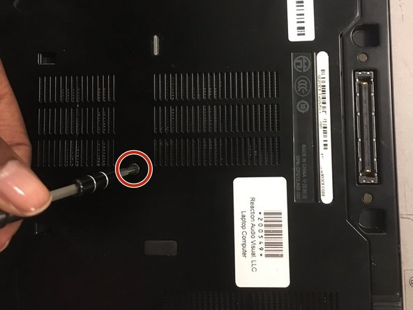 Remove the 8mm screw in the middle from the laptop with the J1 screwdriver.