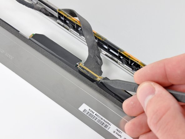 Use the tip of a spudger to flip up the thin steel retaining clip securing the display data cable to its socket on the LCD.