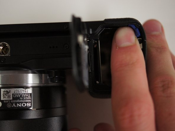 With the battery door open, push the blue lever in the battery compartment to release the battery.