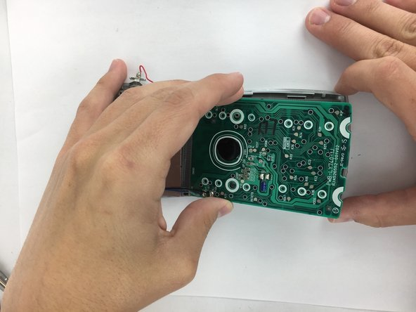 Carefully lift the motherboard, screen, solar panel, and battery terminal combination from the front plate.  Start from the motherboard and lift at an angle toward the solar panel.