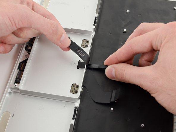 Schiebe den Spudger zwischen das Flachbandkabel zum Trackpad und dem oberen Gehäuse.