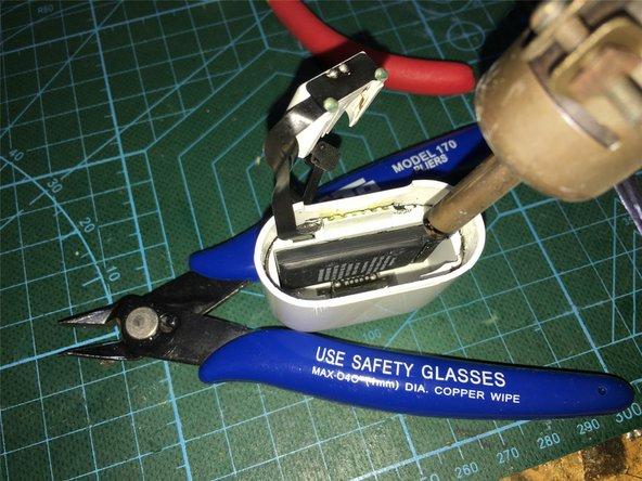继续用热风枪加热后,用撬棒将电池松动部分,把固定连接排线底座上的压扣松动,取出电池