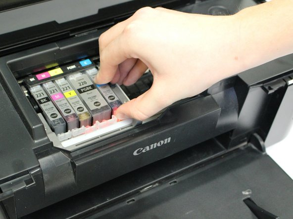 Push in the white clip to release the ink cartridge from the printhead.