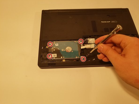 Remove the four 6 mm JIS #0 screws from the hard drive.