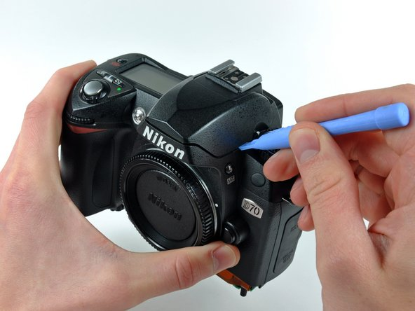 Use a plastic opening tool to carefully pry up the flash unit at the point shown in the picture.
