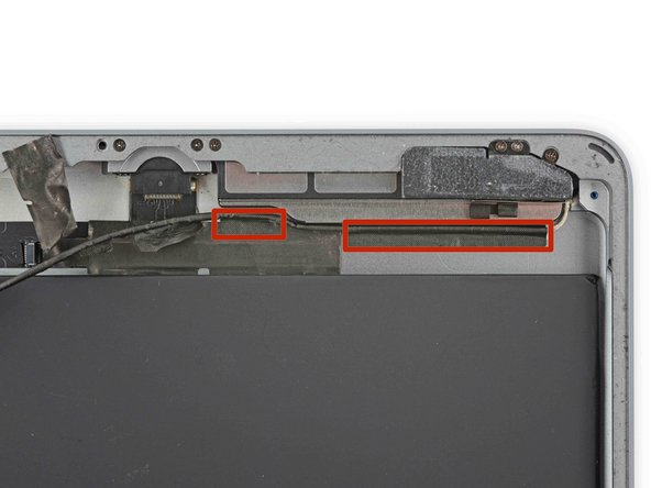 There are two remaining pieces of tape securing the left antenna cable to the rear case.