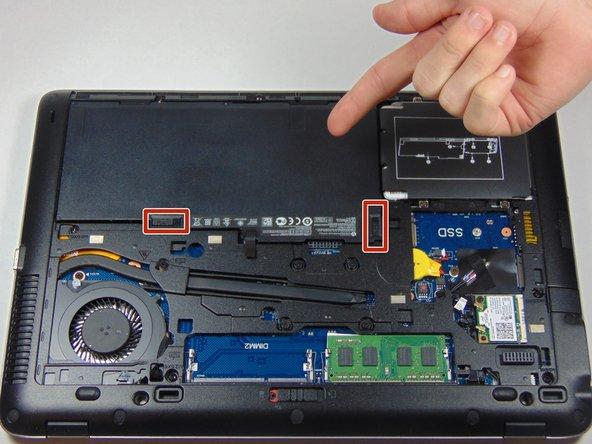 Une fois le cache retiré, vous pourrez voir la batterie et les deux loquets qui la maintiennent en place.