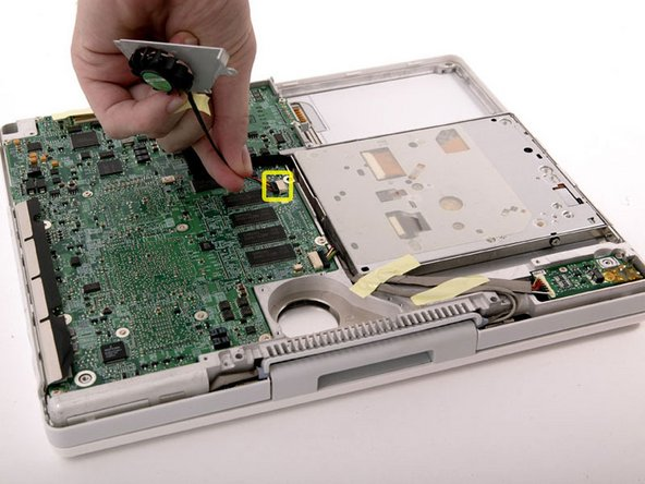 Lift the fan out of its compartment and disconnect it from the logic board, removing tape as necessary.