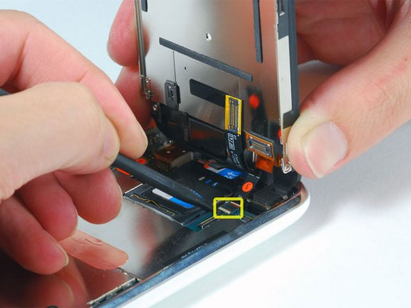 Use a spudger to flip up the white plastic hinged flap holding the remaining ribbon cable in place. The white tab will rotate up 90 degrees, releasing the ribbon cable.