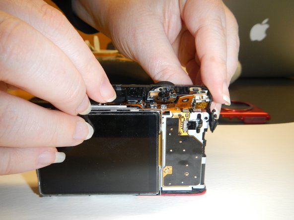 Lift from the back of the camera, angling forward and pull off to remove the power button assembly