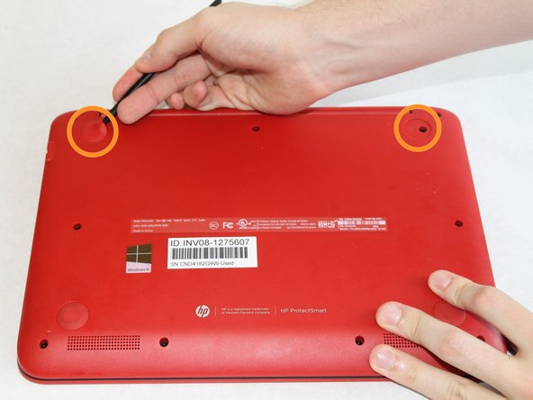 Use the spudger to pry off the two rubber feet near the hinge of the laptop. This will reveal two hidden 9mm screws.