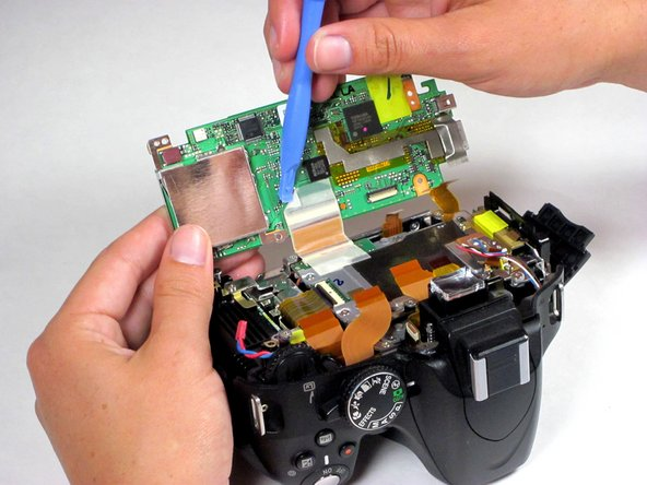 Flip the motherboard out of the camera body and toward the bottom of the device to expose its underside.