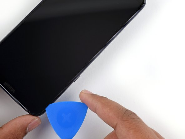 Slide your tool along the left edge of the phone to separate the glue securing the display.