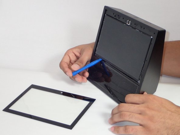 Once the protector is lifted from screen, use the plastic opening tool  to remove the actual screen from device, using an opening near the bottom left corner.