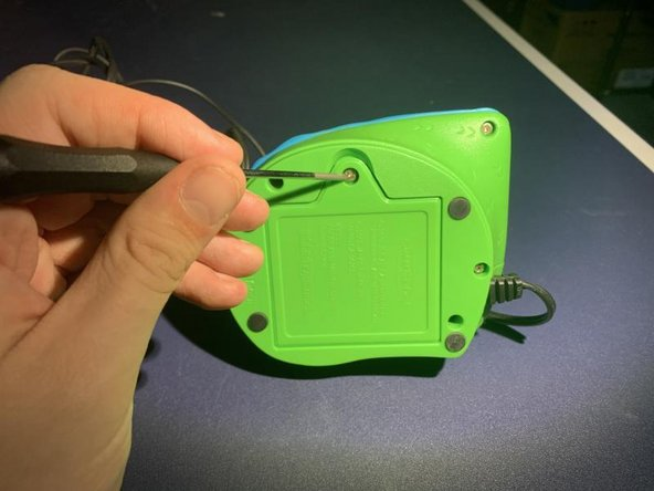 Remove the single screw from the battery panel using a Phillips head screwdriver.