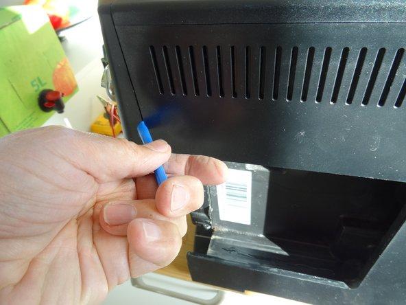 Die linke Seite klemmt ein bisschen. Setze ein Plastiköffnungswerkzeug in den Spalt zwischen Front und linkem Seitenteil über der Öffnung für den Wassertank. Hebele den Spalt etwas größer.