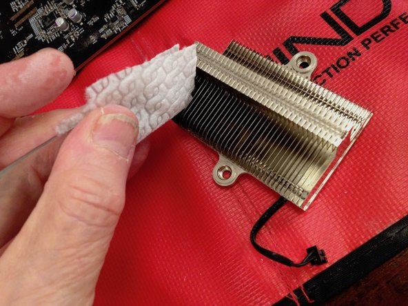 Thoroughly clean the northbridge heatsink. After removing the old thermal paste on the occluding surface clean the fins. First use pressurised air. Then use a dinner knife with lint-free cloth soaked in isopropanol to clean each of the spaces between the fins.