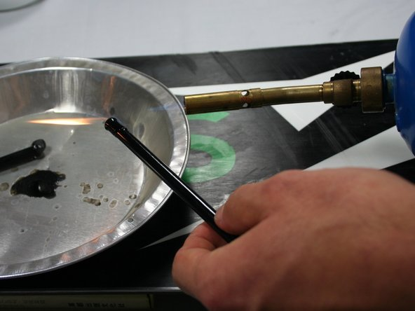 Using a propane torch or a butane lighter, heat up one tip of the P-Tex candle over a metal pan.