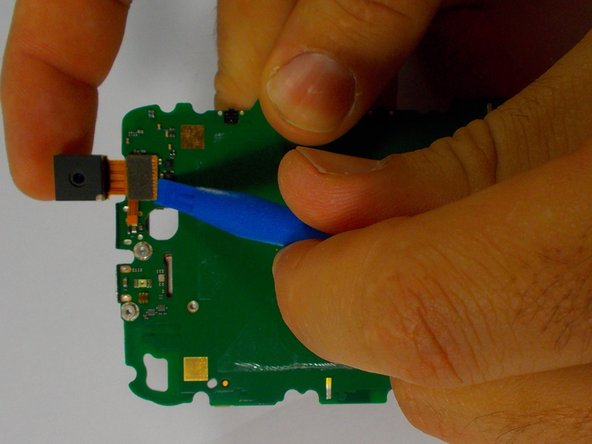 Use the plastic opening tool to lift the ribbon cable connector from the motherboard.