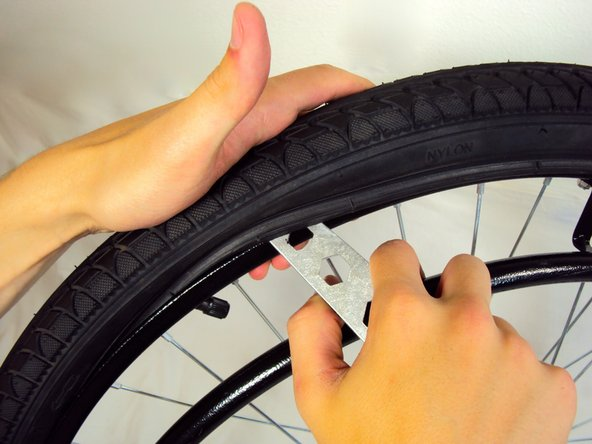 Insert the 19 mm socket wrench between the rubber tire and the metal frame.
