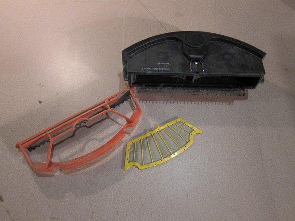 Ouvrez le couvercle rouge du bac à poussière. Retirez les débris du bac.