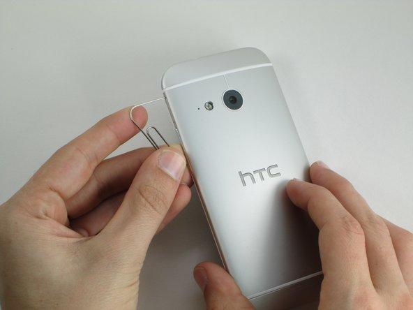 Stecke das Ende einer Büroklammer in die Löcher auf jeder Seite des Telefons, um die SIM-Karte und die Micro SD-Karte auszuwerfen.