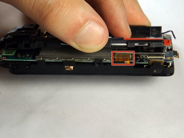 Once the screws are removed, the motherboard can be separated from the other components after prying open the gold-colored clamps hidden underneath the battery compartment.