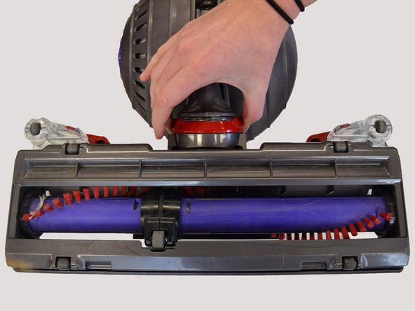 Lay the vacuum on its back and remove the red clip from the bottom front of the vacuum by placing both your thumbs on either side and pulling up.