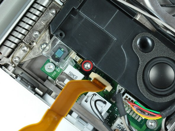 Remove the single T8 Torx screw securing the left speaker to the lower case.