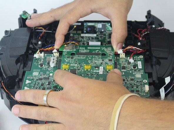 Using both hands, lift the motherboard connected to the camera away from the device's main motherboard.