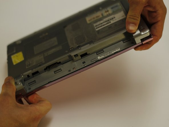 While holding the top of the netbook, flip the netbook over.