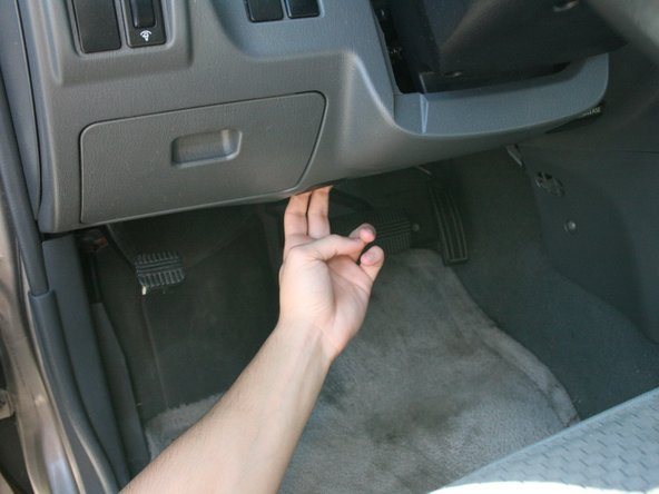 Reach under the driver's cabin panel and pull on the hood release.