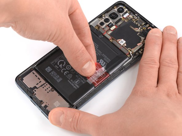 Peel back the red pull tab and the black sticker from the edge of the battery.
