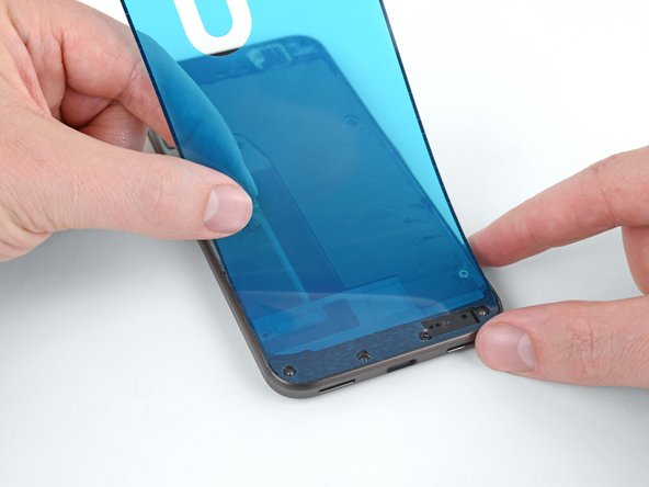Hold the adhesive sheet with the exposed adhesive facing down, and carefully align it into the lower edge of the phone.