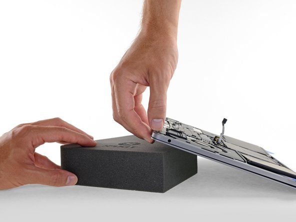 To separate the center battery cell, first raise the back edge of the MacBook Pro and prop it up on a foam block or book, so that the adhesive remover will flow away from the logic board.
