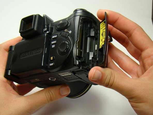 Turn the camera to the side with the memory card slot and open the compartment for the CF card.